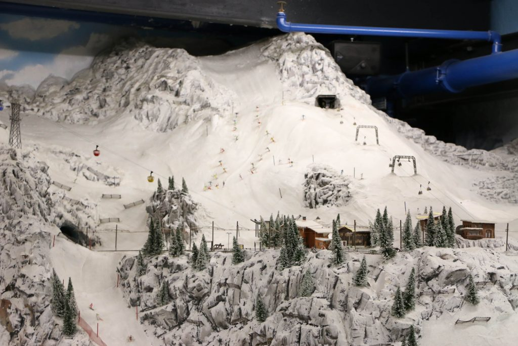 Part of the alps, remodeled in the Miniatur Wunderland. While the focus is clearly on the trains driving around, you can find many other vehicles moving around, like the gondolas on the mountain.